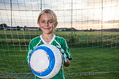 Portrait of smiling young football goalkeeper holding ball on football ground - p300m1580917 by Fotoagentur WESTEND61