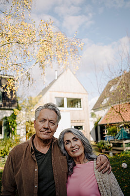 Portrait of senior couple in garden of their home in autumn - p300m2156225 by Gustafsson