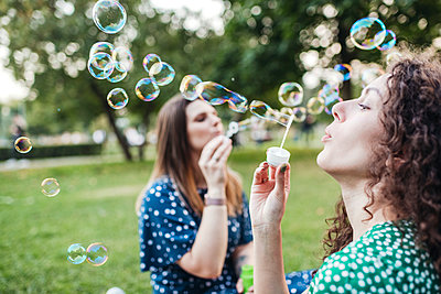 Beautiful female friends enjoying while blowing bubbles from wands at park - p300m2226658 by Katharina und Ekaterina
