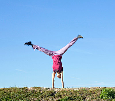Mid adult woman doing cartwheel in a park - p3741487 by Olli-Pekka Orpo