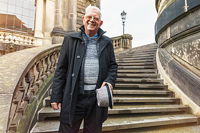 Senior man exploring city standing on stairway, Dresden, Sachsen, Germany - p429m2077850 by Tamboly