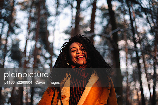 Portrait of happy young woman standing in forest during winter - p1166m2268804 by Cavan Images