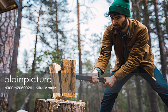 Man chopping wood in rural landscape - p300m2060926 by Kike Arnaiz