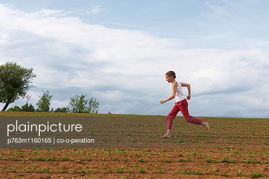Laufendes Mädchen auf dem Feld - p763m1160165 von co-o-peration
