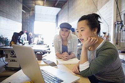 Female design professional engineers brainstorming at laptop in workshop - p1192m1202056 by Hero Images