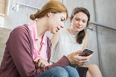 Studentin und Freundin hören Musik mit Kopfhörer - p1284m1452108 von Ritzmann