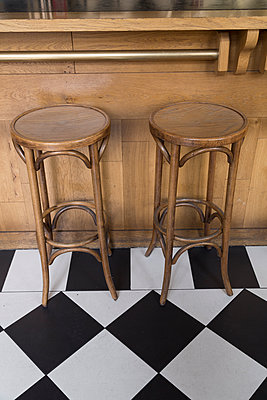 Wooden bar stools and black and white tiles - p1682m2263426 by Régine Heintz
