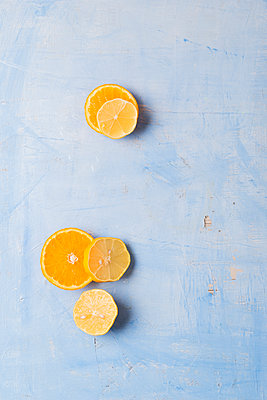 Lemon and orange slices on blue background - p300m1188985 by Mandy Reschke