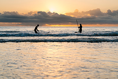 Friends surfing with paddleboard on sea against sky at dawn - p300m2225428 by Ezequiel Giménez