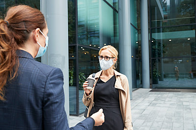 Women wearing face mask while talking against office building - p300m2227072 by Pete Muller