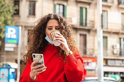 Businesswoman using mobile phone while drinking coffee during COVID-19 - p300m2241062 by NOVELLIMAGE