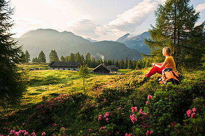 Young woman sitting in alpine meadow and watching landscape - p300m659876f by Hans Huber
