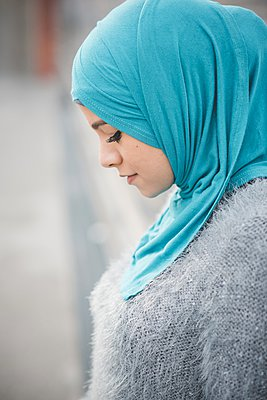 Close up portrait of young woman wearing turquoise hijab on footbridge - p429m1021868f by Eugenio Marongiu