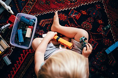 Overhead view of boy sitting on rug playing with toy trains - p429m1105652 by JFCreatives