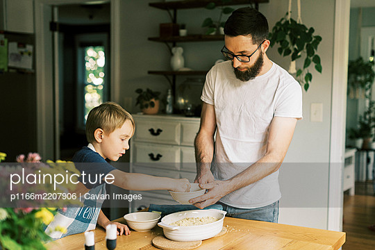 A father and son putting streusel on a peach cobbler - p1166m2207906 by Cavan Images