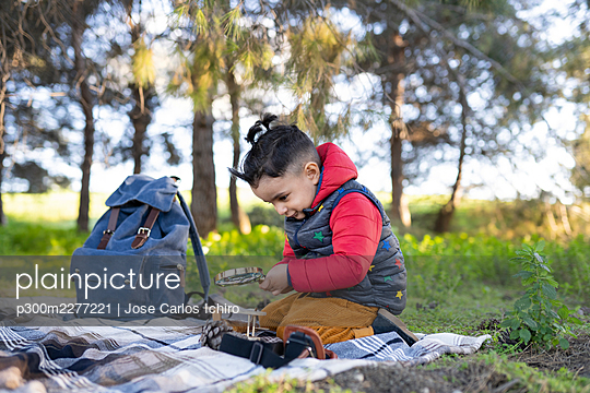 Curious boy searching through magnifying glass while kneeling on picnic blanket - p300m2277221 by Jose Carlos Ichiro