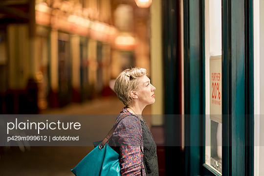 Mature woman looking at shop window at night, London, UK - p429m999612 by dotdotred