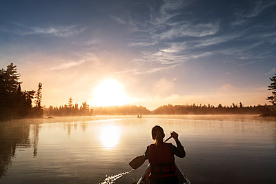 Rear view of woman traveling in boat on calm lake against sky - p1166m1229480 by Cavan Images