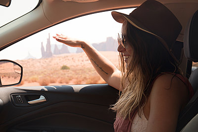 Side view of smiling woman wearing hat and sunglasses while sitting in car at Monument Valley Tribal Park - p1166m2025123 by Cavan Images