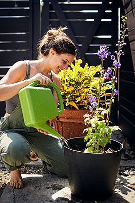 Mid adult woman watering plant at backyard - p1166m2094622 by Cavan Images