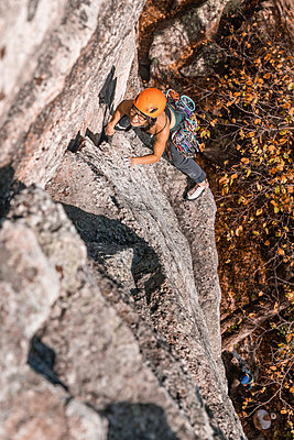Woman climbing in the fall in the Gunks - p1166m2113014 by Cavan Images