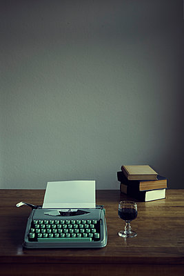 Typewriter with paper and glass of wine on table top - p1312m2156125 by Axel Killian