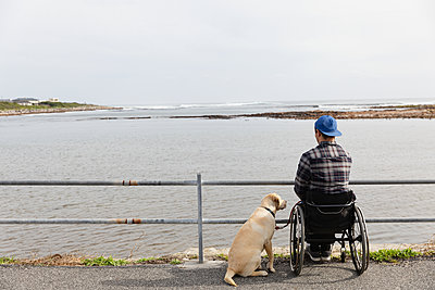 Disabled man in a wheelchair enjoying a day out - p1315m2131521 by Wavebreak