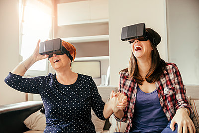 Excited adult daughter with mother at home wearing VR glasses - p300m1356394 by Zeljko Dangubic