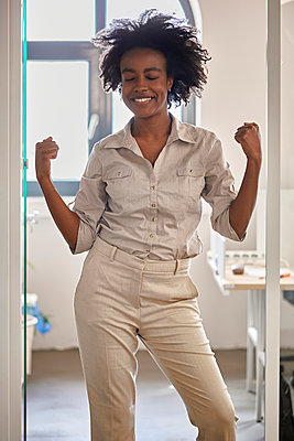 Cheerful businesswoman flexing arms while standing at doorway in office - p300m2282744 by Zeljko Dangubic