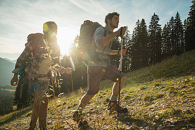 Austria, Tyrol, Tannheimer Tal, young couple hiking in sunlight on alpine meadow - p300m980975f by Uwe Umstätter