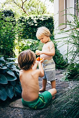 Boys on garden path eating oranges, Bludenz, Vorarlberg, Austria - p429m1105769 by JFCreatives