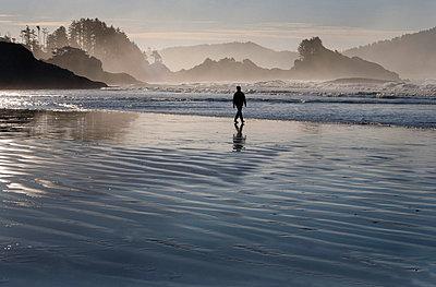 A man walking along Chesterman's Beach near Tofino on Vancouver Island British Columbia Canada - p4426510f by Design Pics
