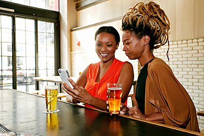 Black women using cell phone at bar - p555m1305269 by Peathegee Inc