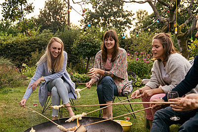 Friends roasting campfire bread in the allotment garden - p788m2037446 by Lisa Krechting