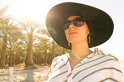 Portrait of woman wearing sunglasses and sunhat looking away, Palm Springs, California, USA - p924m1422796 by Raphye Alexius