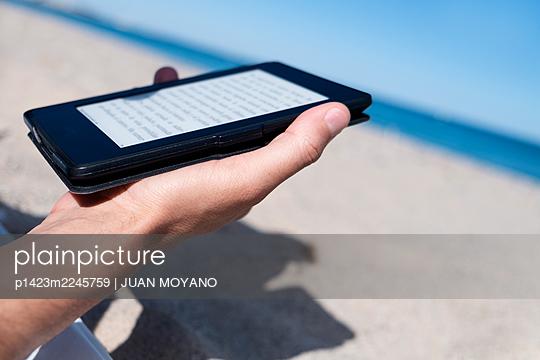 Man using an e-reader on the beach - p1423m2245759 by JUAN MOYANO