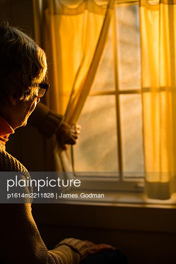 Ältere Frau schaut aus dem Fenster - p1614m2211828 von James Godman