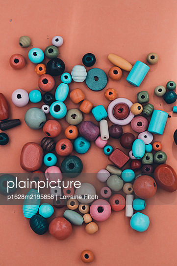 Coloured beads on plain coloured background - p1628m2195858 by Lorraine Fitch