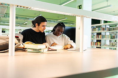 Two students with laptop and books learning in a library - p300m2167567 by Valentina Barreto