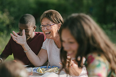 Happy senior woman having lunch with family in backyard during garden party - p426m2036590 by Maskot