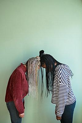 Zwei junge Frauen stehen Kopf an Kopf - p427m2063916 von Ralf Mohr