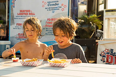 Two young boys eating fast food beside fast food trailer - p924m1180341 by Ian Spanier