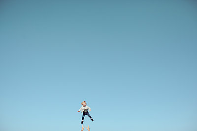 Distant view of female toddler thrown mid air against vast blue sky - p924m1422872 by Sasha Gulish