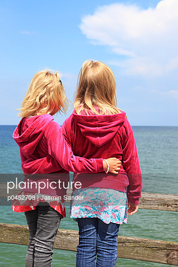 Twin girls by the sea - p0452708 by Jasmin Sander