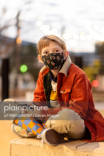 Teen sitting holding phone wearing mask during Global Pandemic - p1166m2269367 by Cavan Images