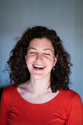 Woman in selfquaratine laughing - p1295m2173184 by Katharina Bauer