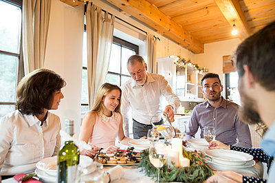 Senior man pouring water into glass at Christmas dinner table - p300m1505665 by HalfPoint