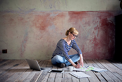 Woman sitting on wooden floor in an unrenovated room of a loft working - p300m2070751 by Rainer Berg