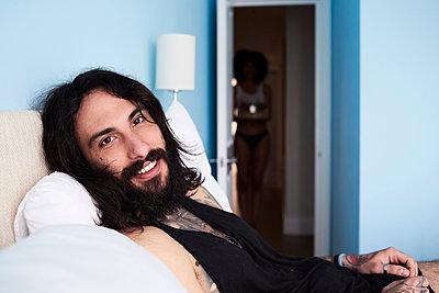 Portrait of smiling tattooed man lying n bed with girlfriend in background - p300m2103602 von Ivan Gener