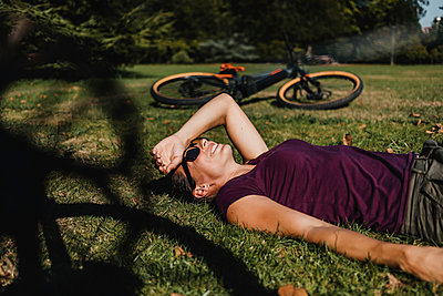 Woman lying on grass while resting by mountain bike at park - p300m2240169 by David Molina Grande